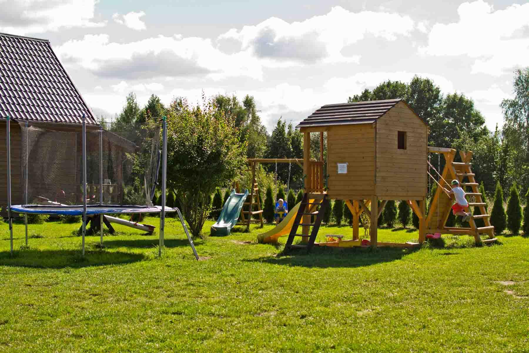 Plac zabaw dla dzieci z domkiem, piaskownicą, trampolinami oraz huśtawkami